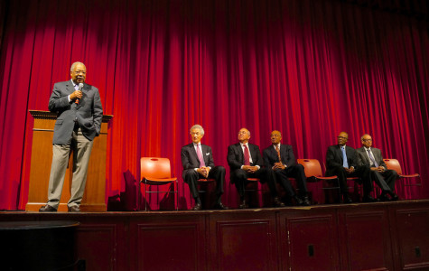 Rutgers University professor Clement Price Ph.D speaks in front of the school on stage with esteemed guests.