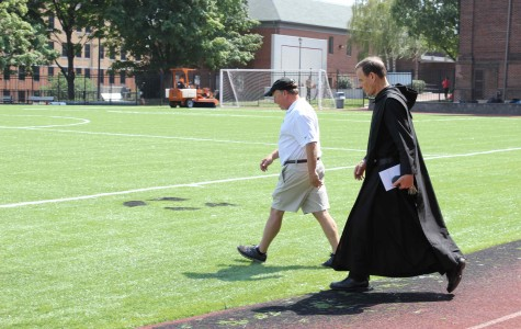 Headmaster Rev. Edwin Leahy strolls onto the newly laid turf to examine the handiwork.