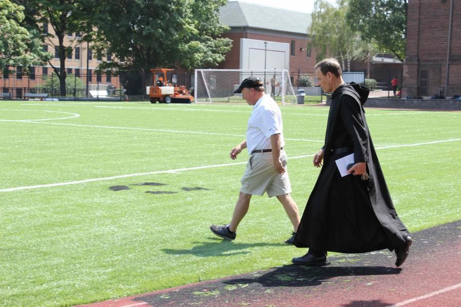 Headmaster Rev. Edwin Leahy strolls onto the newly laid turf to examine the handiwork.