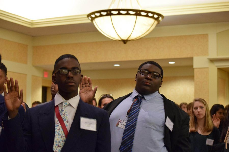 UDII Justin Dickerson (to the left) and Senior Jonathan Lewis (to the right) being sworn into the Youth and Government conference.