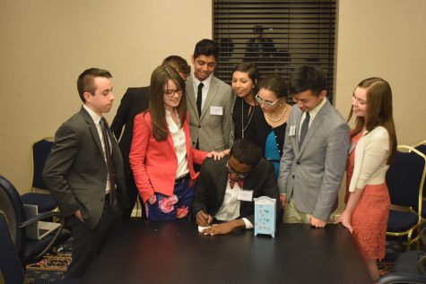 Senior Mahishan Gnanaseharan, Governor of 2016 YMCA Youth and Government Conference, with his cabinet signing a bill into law.