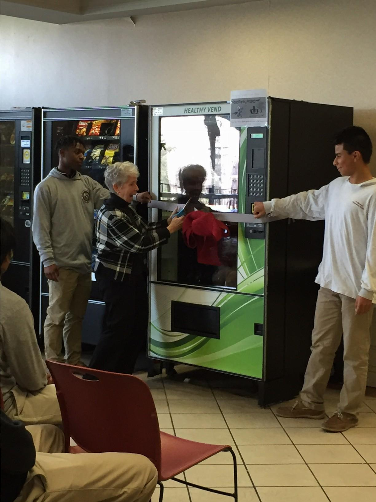Sister Linda stands with freshman to celebrate the new vending machine. Eighty percent of the proceeds will go to the food pantry.