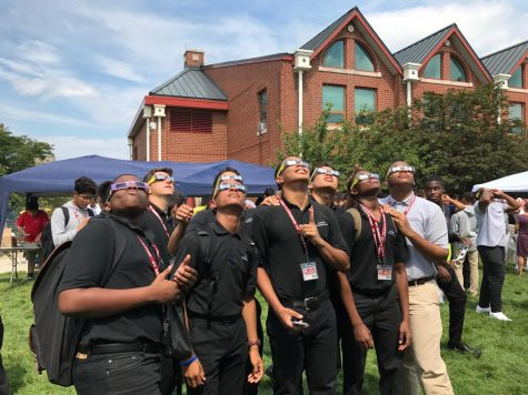 SBP students gather on Leahy Field wearing safety glasses to take in a rare solar eclipse