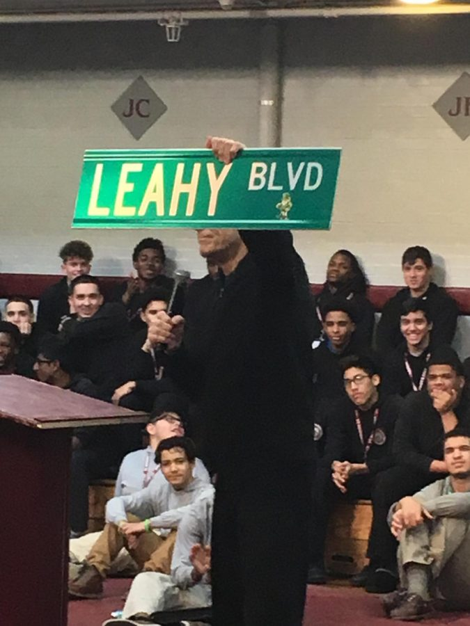 Fr. Edwin Leahy brandishes street sign at convo January 10, 2018.