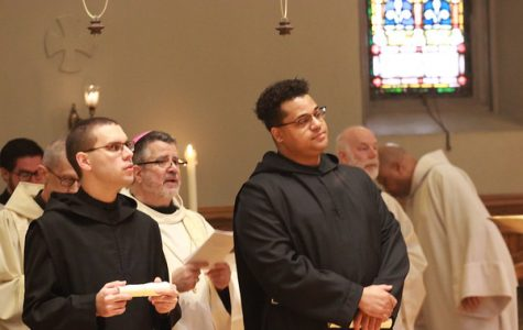 As members of the St. Benedict's community watch via live stream, Benedictine monks Br. Asiel Rodriguez (left) and Br. Simon Clayton profess their solemn vows. Health protocols due to the coronavirus barred a celebration and public viewing.